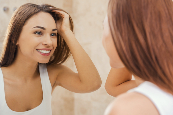 Good morning! Beautiful young woman touching her hair with hand and smiling while standing in front of the mirror