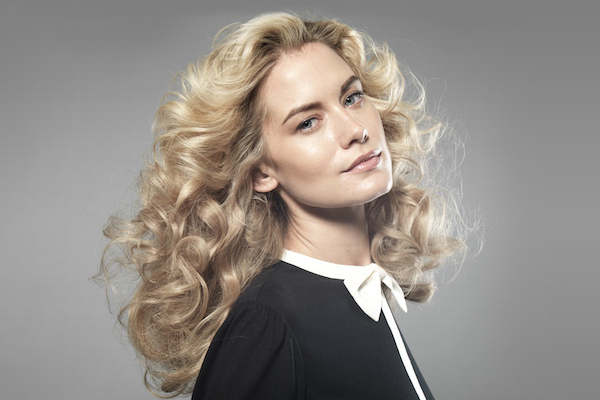 Blonde Woman Showing Off Her New Curly Clip In Hair Extensions
