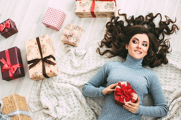 Woman With A Pretty Hairstyle Using Tape-In Hair Extensions At Holiday Party
