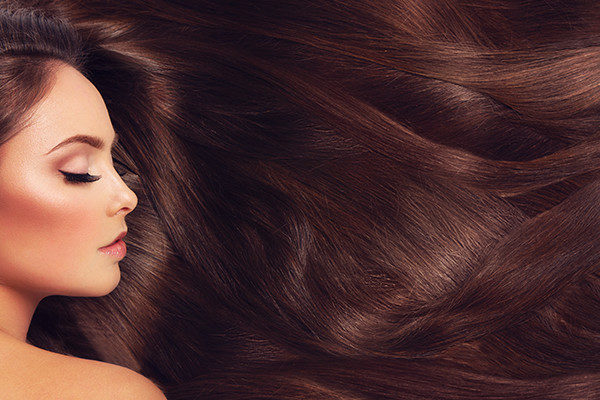 Lady with dark red hair with professional hair extensions to make a lasting impression